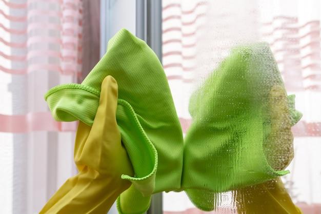 Handen met een stofdoek die de spiegel schoonmaken