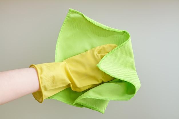 Handen met een stofdoek die het glas schoonmaken