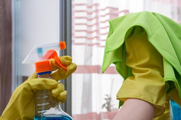 Handen met een stofdoek en afwasmiddel die de spiegel schoonmaken