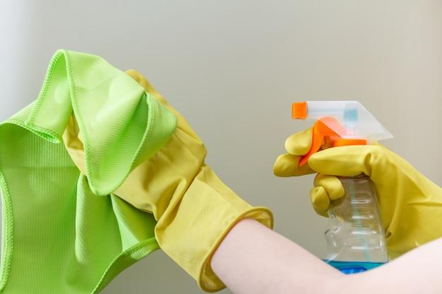 Handen met een stofdoek en afwasmiddel reinigen het glazen oppervlak