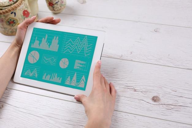 Handen met een tablet liggend op de houten tafel
