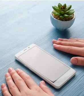 Handen met een telefoon op de tafel. een vrouw heeft een telefoon in haar handen.