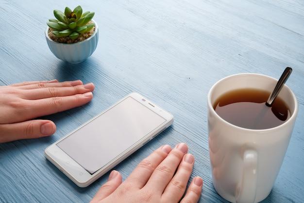 Handen met een telefoon op de tafel. meisje houdt de telefoon in haar handen.