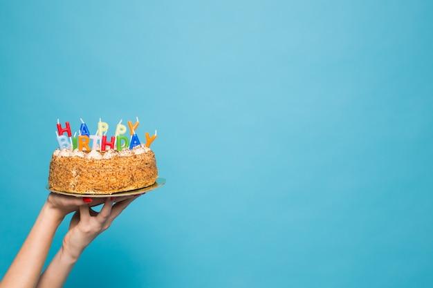 Handen met een verjaardagstaart met kaarsen en de inscriptie verjaardag op een blauwe ondergrond. gefeliciteerd met het jubileum en de verjaardag. copyspace