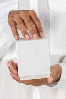 Handen met een witte lege cosmetische verpakking