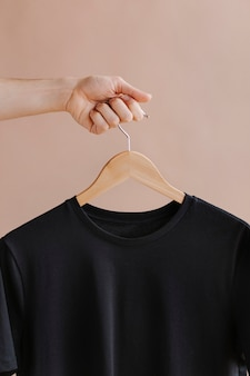 Handen met een zwart t-shirt in een hanger