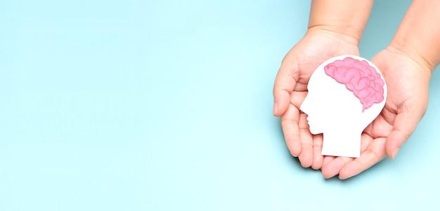 Handen met encefalografie hersenen papier knipsel.