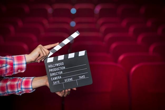 Handen met filmklapper in de bioscoop