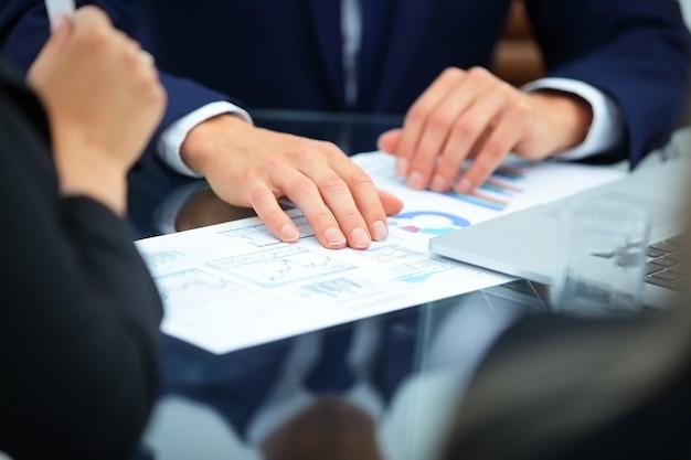 Handen met financiële schema's van econoom