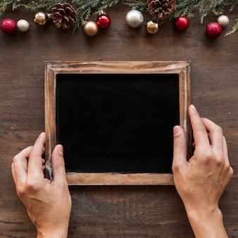 Handen met fotolijst in de buurt van kerstversiering