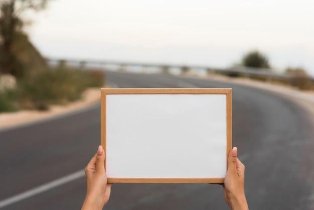 Handen met frame op de weg