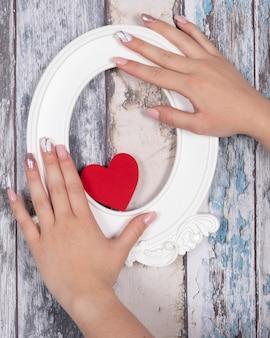 Handen met gelnagels die een rood hart en een wit frame houden
