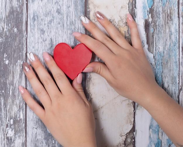 Handen met gelnagels die een rood hart houden