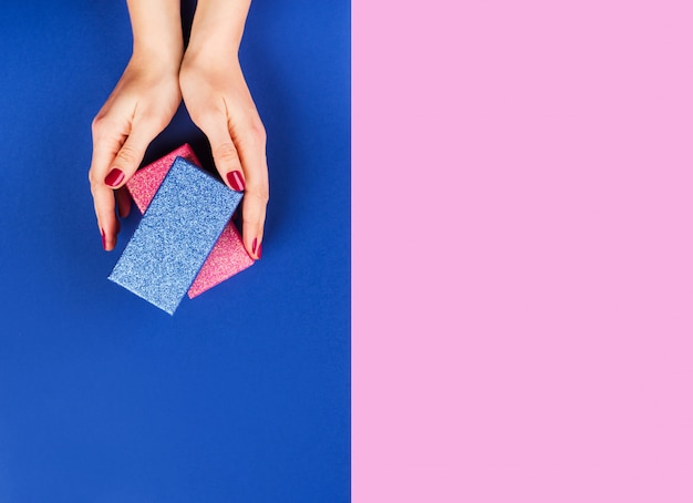 Handen met geschenkdoos op roze en klassieke blauw