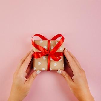 Handen met gewikkeld geschenk met rood lint