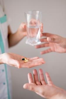 Handen met glas water en pillen