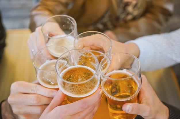 Handen met glazen bier en juichen