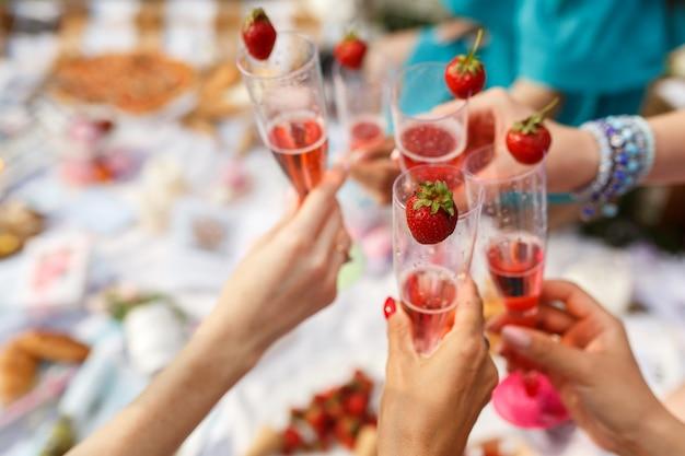 Handen met glazen proost op de picknick van de zomerdag