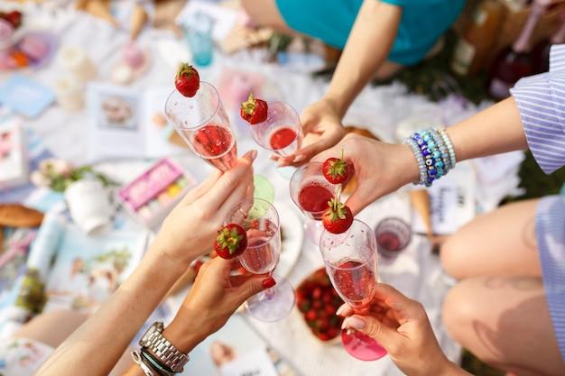 Handen met glazen proost op de picknick van de zomerdag.