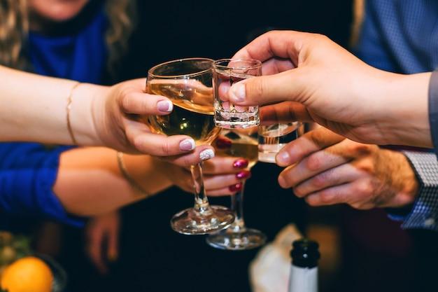 Handen met glazen wijn en wodkavrienden vieren