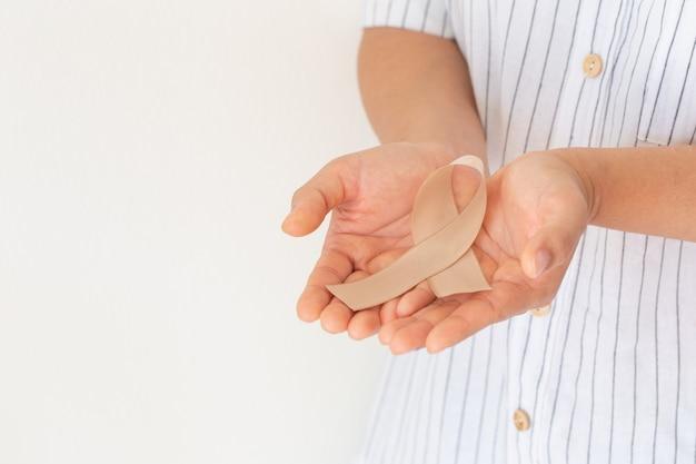 Handen met gouden lint op witte achtergrond. het internationale bewustzijnssymbool voor het concept van kanker bij kinderen.