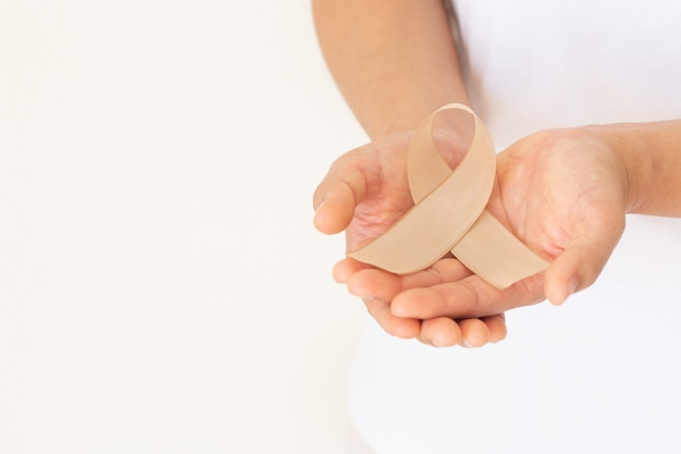 Handen met gouden lint op witte achtergrond voor kanker bij kinderen.