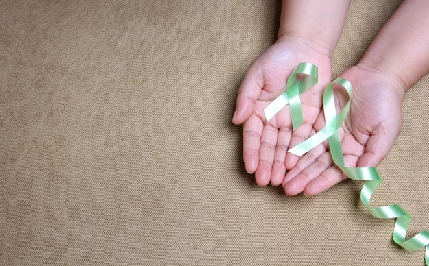 Handen met groen lint met kopie ruimte.