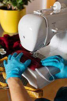 Handen met handschoenen die de maskers van een doekgezicht beëindigen