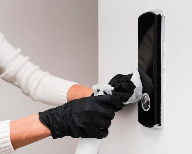 Handen met handschoenen die deurbel desinfecteren