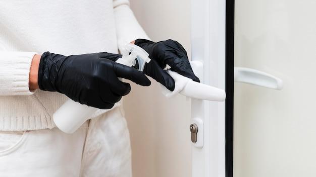 Handen met handschoenen die deurkruk ontsmetten