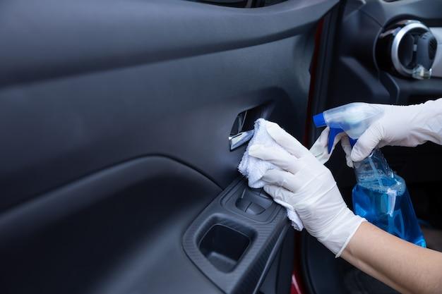 Handen met handschoenen die een autodeur met verstuiver desinfecteren