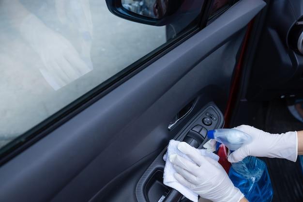 Handen met handschoenen die een autodeur met vod en verstuiver binnen desinfecteren