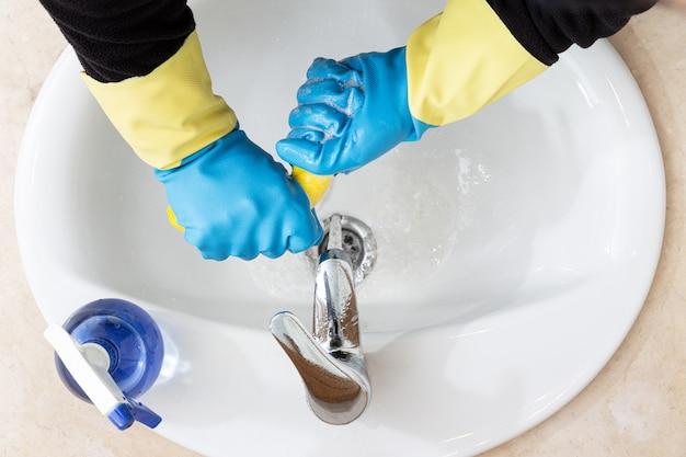 Handen met handschoenen die een badkamers met een geel vod schoonmaken. desinfectie of hygiëneconcept