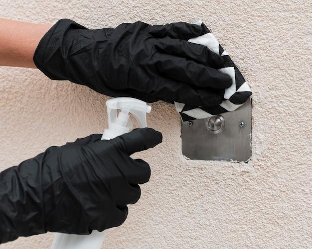 Handen met handschoenen die het oppervlak desinfecteren