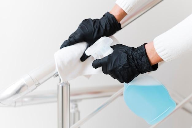 Handen met handschoenen die leuning ontsmetten