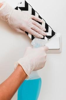 Handen met handschoenen die lichtschakelaar desinfecteren