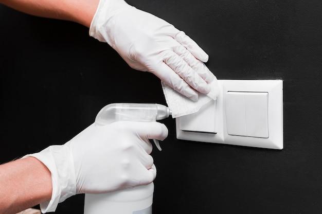 Handen met handschoenen die lichtschakelaars desinfecteren