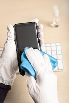 Handen met handschoenen die mobiele telefoon met ontsmettingsmiddel schoonmaken. covid-19 coronavirus uitbraak concept ter voorkoming van besmetting