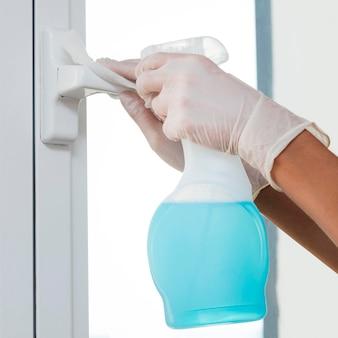 Handen met handschoenen die raamgreep ontsmetten