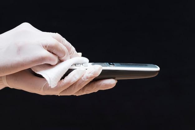 Handen met handschoenen die telefoon desinfecteren