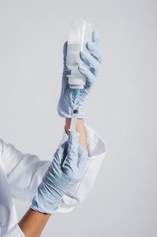 Handen met handschoenen en vaccin