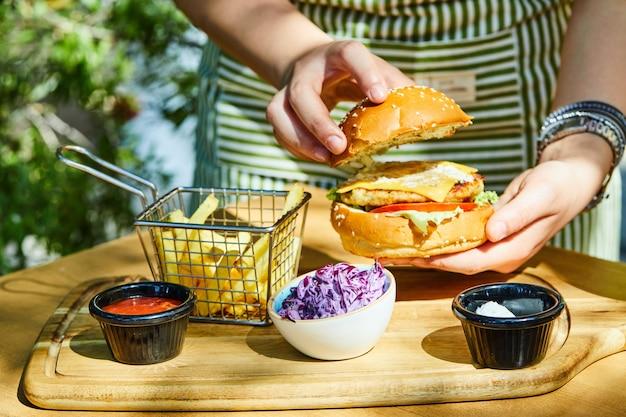 Handen met heerlijke verse hamburger met frietjes en saus op houten tafel.
