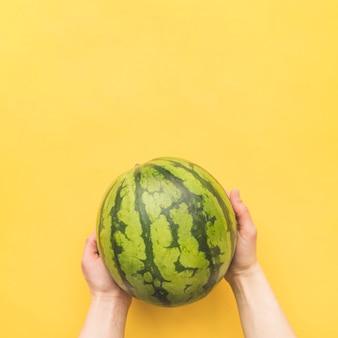 Handen met hele watermeloen