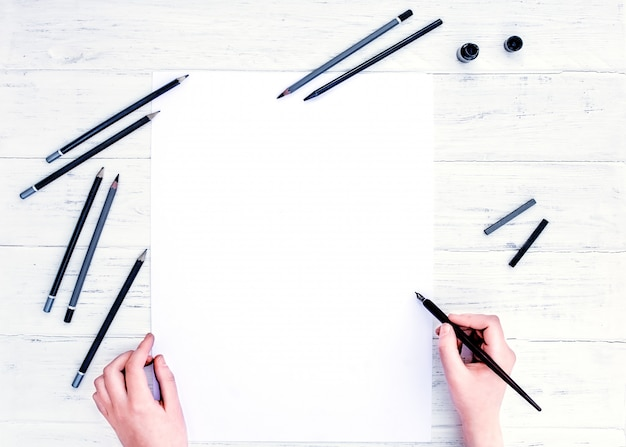 Handen met het lege vel wit papier en een kalligrafie-pen
