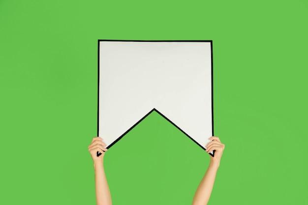 Handen met het teken van bladwijzer op groene muur.