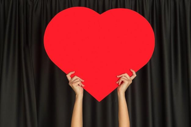 Handen met het teken van hart op zwarte achtergrond.