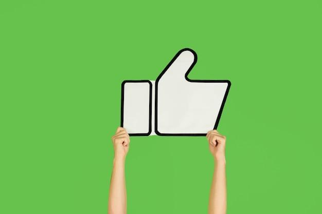 Handen met het teken van like op groene achtergrond