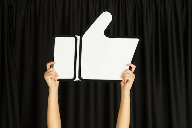 Handen met het teken van like op zwarte achtergrond