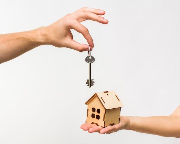 Handen met houten huis en sleutel