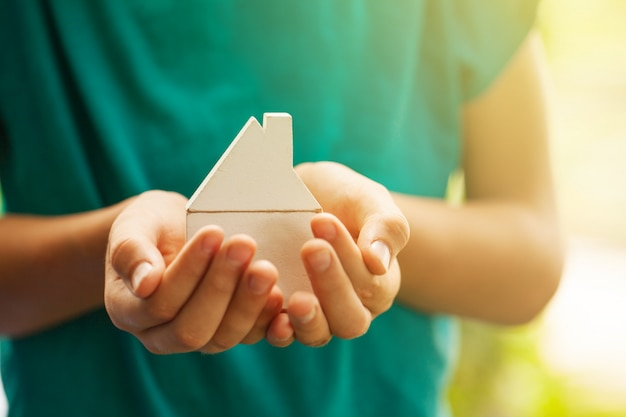 Handen met houten huis model. een nieuw concept voor woning- en woningverzekering kopen.